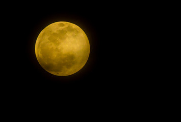 The full moon and its orange brightness is photographed in the night sky from Arizona.