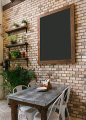 Empty Black Board on Brick Wall and Dinning Table in below.