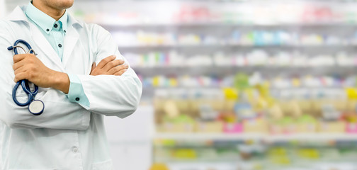 Papiers peints Pharmacie Male pharmacist standing in the drugstore pharmacy. Medical healthcare and pharmaceutical service.