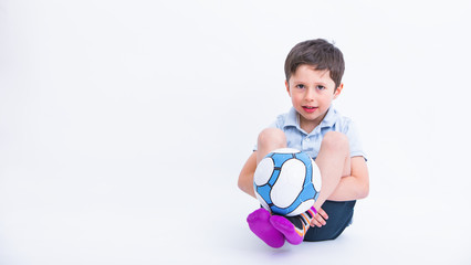 Portrait of the cute little boy playing football, isolated on studio white background. Adorable kid in sport activity, holding a soccer ball. Outdoor or indoor kids activities.
