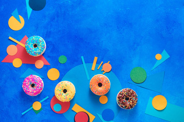 Donuts with colorful paper decorations. Color blocking flat lay header with sweets. Creative food...