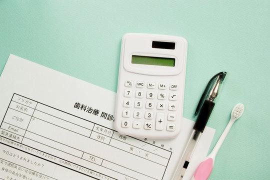 歯の治療の問診票と歯ブラシ・計算、歯医者の予約と料金