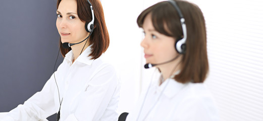 Call center. Group of operators at work. Focus on young brunette woman. Business  concept