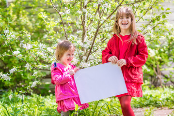 Two laughing sisters stand near the apple tree and hold a white sheet of paper. Springtime in the countryside.