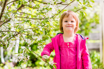 Portrait of smiling 2,5-years old girl with branch of a flowering apple tree. Springtime in the countryside.