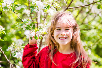 Portrait of smiling 7-years old girl with branch of a flowering apple tree. Springtime in the countryside.