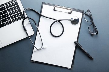 Modern medical technology and sofware advances concept. Doctor's working table with stethoscope acoustic device, keyboard, blank medical record. Close up, copy space background, top view, flat lay.