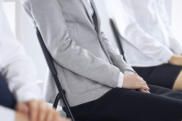 Business people waiting for job interviews or taking part at conference in office, close-up. Women sitting on chairs like at queue or meeting Fototapete