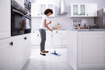Happy Janitor Cleaning Floor With Mop