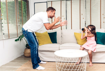 Father with little daughter having fun and playing together on the sofa at home.little girl hug daddy.Love of family and father day concept