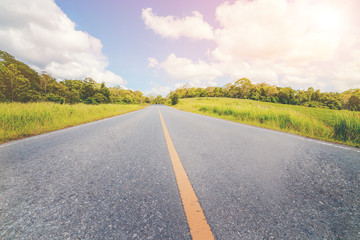 Highway road up hill through green grass field under white clouds on blue sky in summer day. Road trip travel concept.