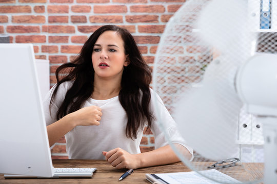 Businesswoman Try To Cool Herself By Fan At Workplace