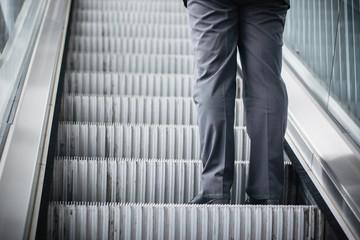 A Man on a moving escalator.