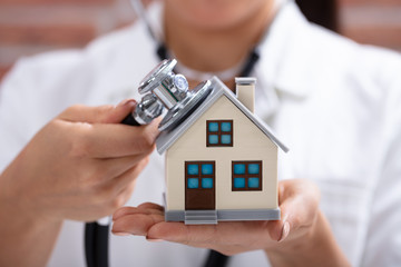 Doctor Using Stethoscope To Check Model House