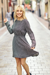 Funny young blonde woman standing on urban background.