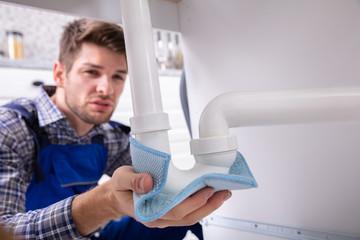 Plumber Holding Napkin To Stop Sink Pipe Leakage