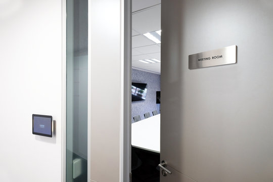 Door with knob opening to the meeting room, with status monitoring and controlling electronic device in front of the room