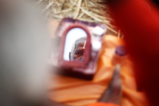 """A Sadhu or Hindu holy man looks into the mirror after taking a holy dip during """"Kumbh Mela"""" or the Pitcher Festival, in Prayagraj, previously known as Allahabad"""