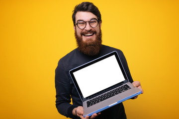Happy man in gray shirt showing laptop computer screen at the camera over yellow background