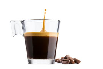 Black coffee in glass cup with coffee beans and  jumping drop on white background