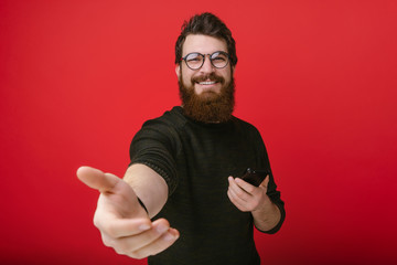 Portrait of cheerful bearded man .stretches his hand, inviting handsome