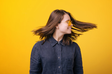 Portrait of a happy young woman spinning her head isolated over yellow background.