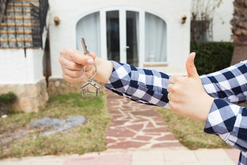 New home, house, property and tenant - Real estate agent handing a house key and showing thumbs up