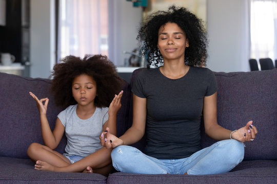 Mindful african mom with cute funny kid daughter doing yoga exercise at home, calm black mother and mixed race little girl sitting in lotus pose on couch together, mum teaching child to meditate