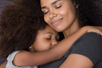 Loving single black mother hugs cute daughter feel tenderness connection, happy african mum caressing embracing little girl, mommy kid cuddle, warm relationships, child custody, foster care concept