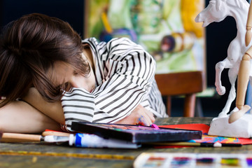 Young woman artist is falling asleep in her workshop.  Closeup of creative workplace on wooden table with drawing tools, pencils, pastels, tubes, watercolors, paintbrushes, sketches.  Art concept.