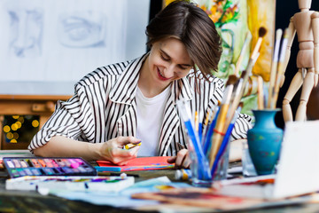 Young beautiful smiling artist teacher student woman girl boy in art workshop studio surrounded by colorful black white sketch painting tools drawing with pastel chalk art canvas artistic masterpiece