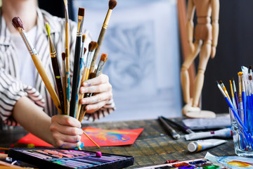 Woman artist at her creative workplace holds bunch of used wooden paintbrushes in soiled with paints hands. Workshop with painting tools and paintings on easels on background. Art concept.