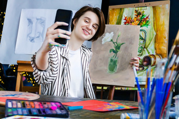 Young beautiful smiling artist teacher student woman girl boy in art workshop studio surrounded by colorful black white sketch painting tools take selfie hold huge art canvas with artistic masterpiece