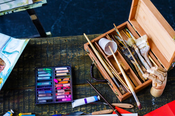 Top view of artists creative workplace on antique table with different drawing tools, soiled with paints brushes, colorful pastels, tubes, paper and pictures, wooden box and hand model. Art concept.