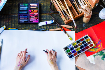 Soiled artists hands is painting on blank paper sheet. Top view of creative workplace on old wooden table with different painting tools, brushes, colorful paints, pastels, tubes. Art concept.