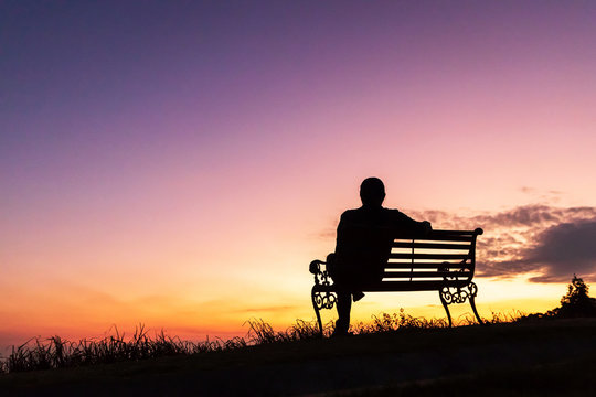 Silhouette of woman sitting alone on the bench against twilight sky over a mountain.