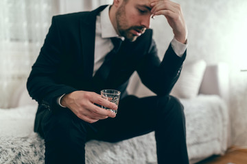 Stressed businessman sitting on the couch in suit, drinking alcohol and holding hand on head.