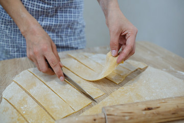 On the table lies the dough for noodles and the tools needed for cutting. The girl cuts small pieces.