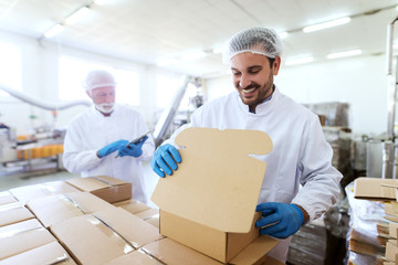 Young Caucasian employee in sterile uniform packing goods in boxes. In background supervisor holding tablet and counting boxes.