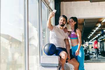 Cute sporty couple taking selfie with smart phone in gym.