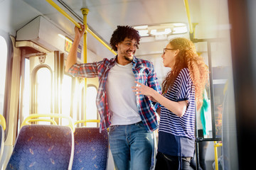 Young cute couple standing in a bus and talking. Mix race couple .