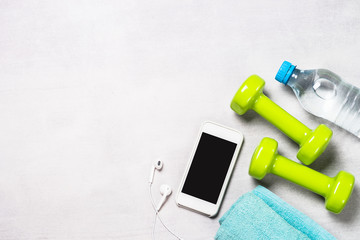 Dumbbells, measuring tape, water and apple top view.