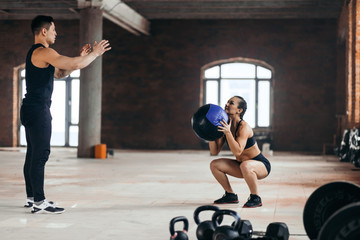 Beautiful young sports couple is working out with medicine ball in gym. hobby, interest, lifestyle