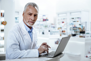 Dark-eyed caucasian pharmacist in a white coat working on a laptop