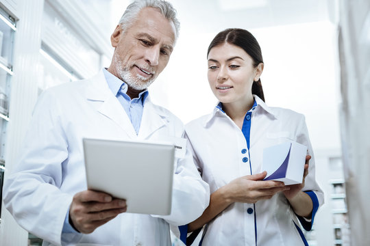 Handsome bearded man in a white coat showing a picture on a tablet