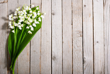 Tuinposter Lelietje van dalen bouquet of lily of the valley on old weathered wooden table background