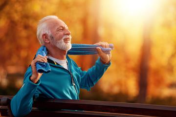 Senior runner doing stretching in park