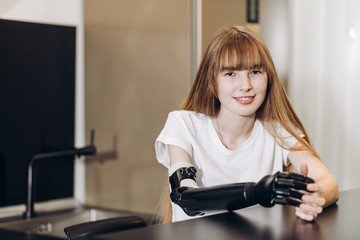 smiling awesome girl with artificial arm looking at the camera indoors. close up photo, copy space
