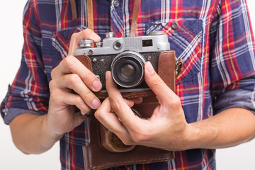 Vintage, photographer and hobby concept - close up of retro camera in man's hands over the white background