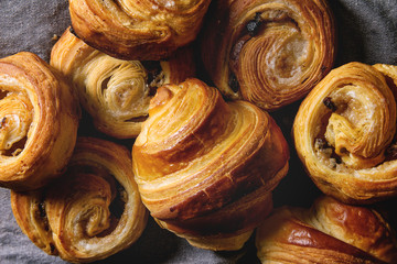 Variety of homemade puff pastry buns cinnamon rolls and croissant over grey cloth. Flat lay, cloth up Fototapete